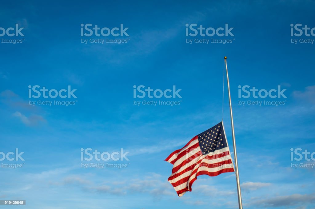 American Flag at Half Mast after another School Shooting wide angle view with Flag lowered on Flagpole stock photo
