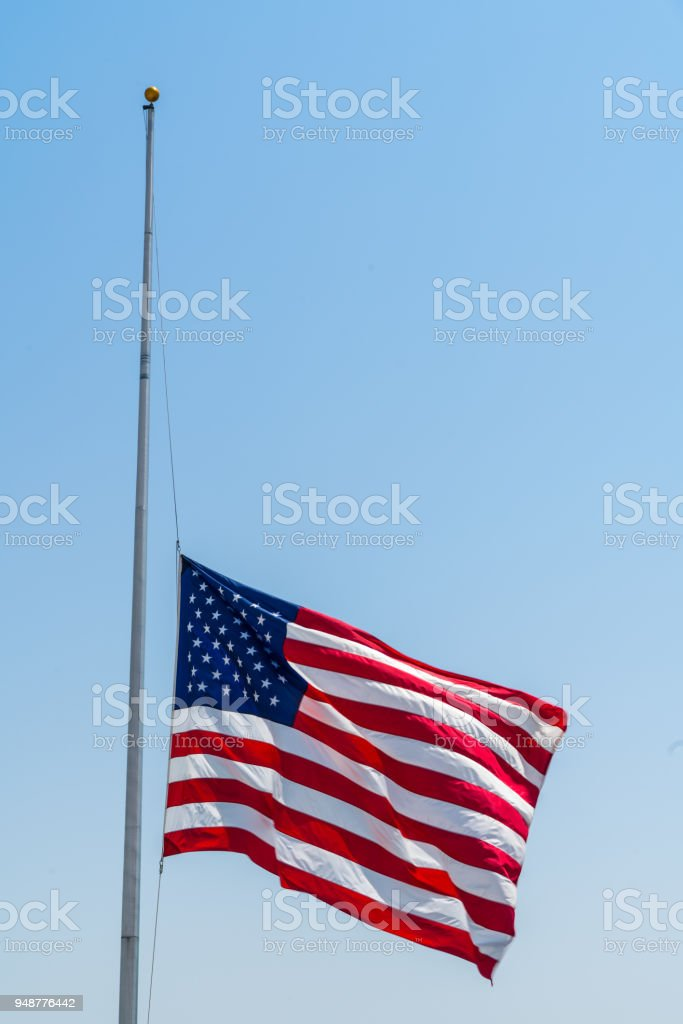 American flag at half mast after memorial services stock photo