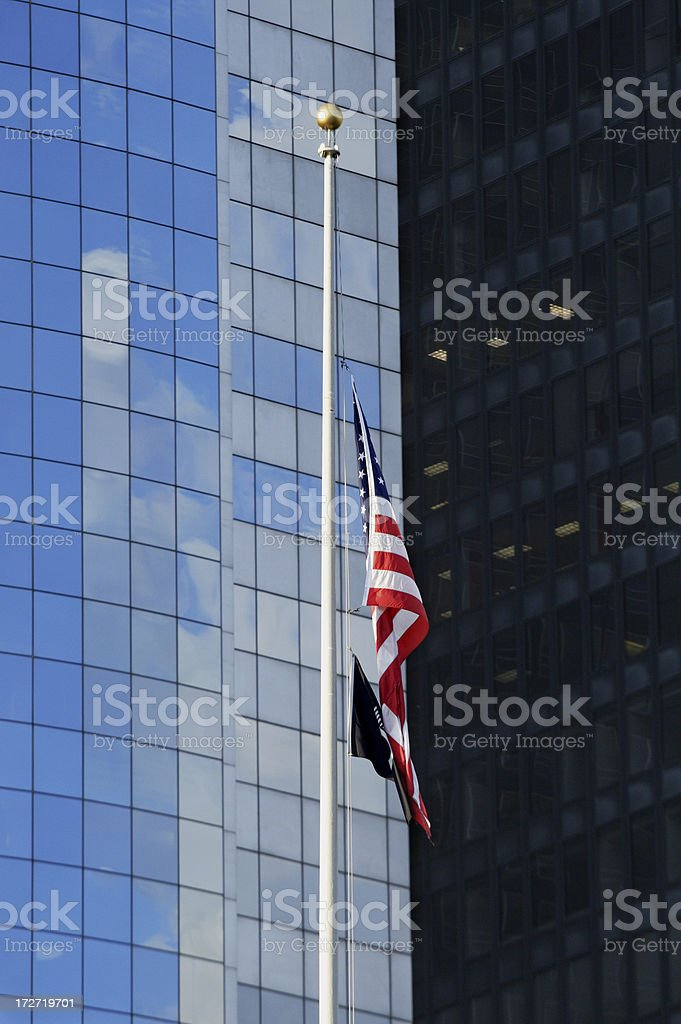 American flag at half mast against modern skyscrapers stock photo