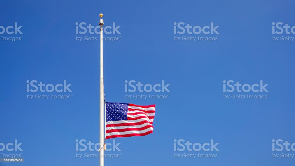 American Flag at Half Mast aka Half Staff Against Clear Blue Sky stock photo