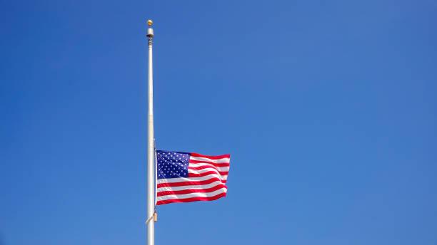 American Flag at Half Mast aka Half Staff Against Clear Blue Sky stock photo