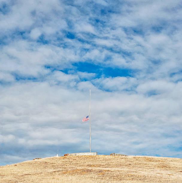 American Flag at Half Mast on Hill stock photo