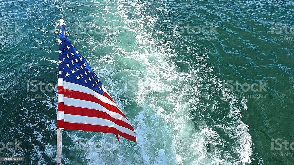 American flag at stern of yacht... stock photo
