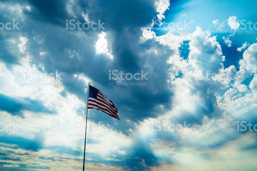 American flag backlit by a stormy looking sky stock photo