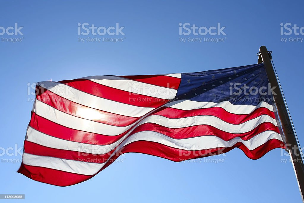 american flag backlit from the sun stock photo