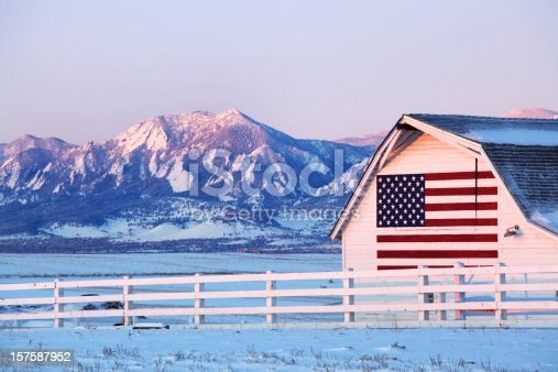 Barn with American Flag painted on side, in front of Boulder Flatirons.