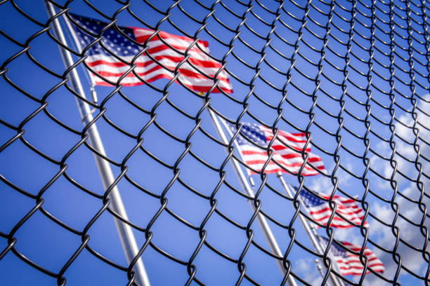 American flag behind wired fence. Conceptual photo. Border wall to USA stock photo