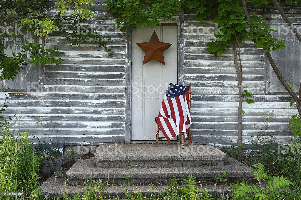 American flag by weathered house door stock photo