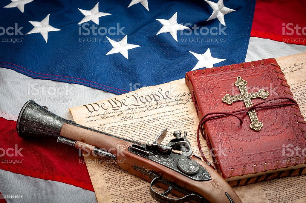 American flag, Constitution, flintlock pistol, red bible and gold cross stock photo