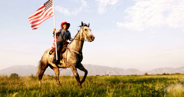 American Flag Cowgirl Young woman riding horse carrying American flag in grassy green field with mountains in the background. appaloosa stock pictures, royalty-free photos & images