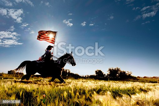 Young woman riding horse carrying American flag in grassy green field with mountains in the background.