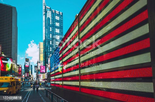 American flag displayed on a digital billboard at Times Square New York City, while pedestrians and cars are passing by on the street. Seen a summer day in May.
