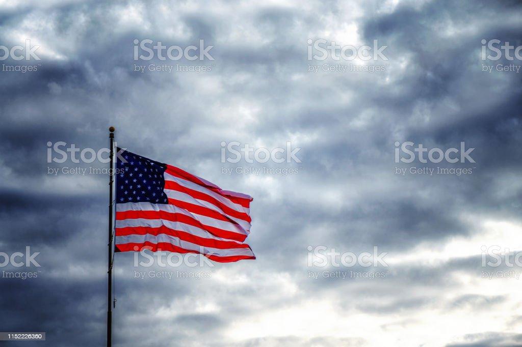 American flag flapping in dark ominous sky