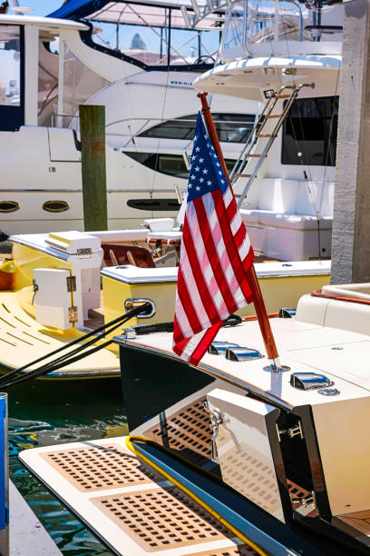 American flag flies from the rear flag pole on a boat at the marina in Sarasota FL, USA stock photo