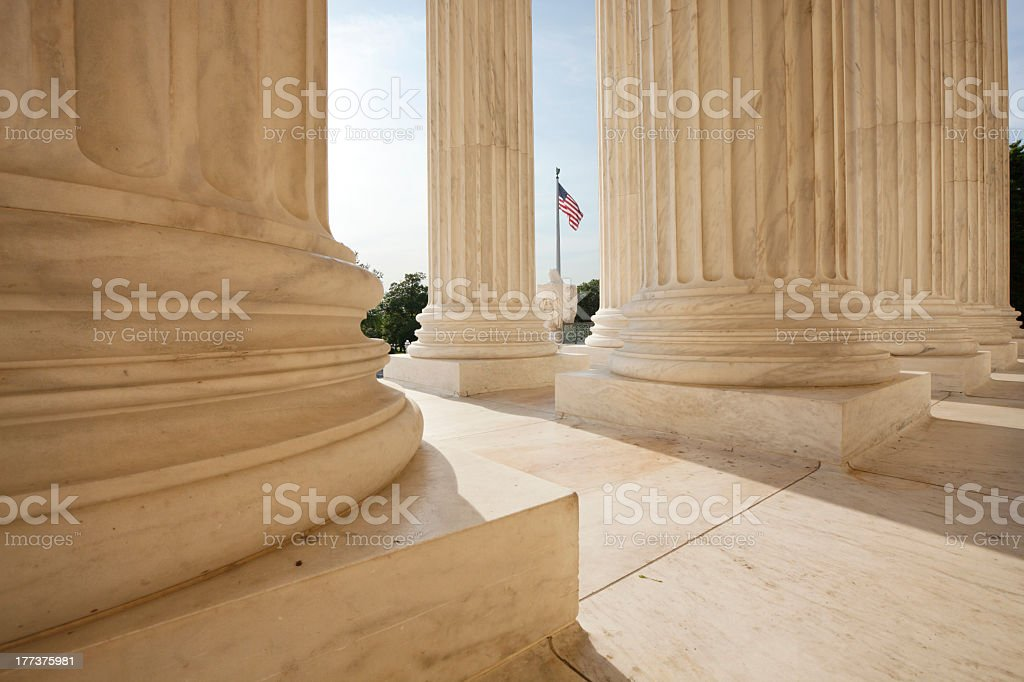 American flag flying between Supreme Court building pillars stock photo