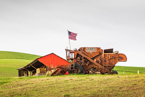 American flag flying from an antique combine wheat harvester. stock photo