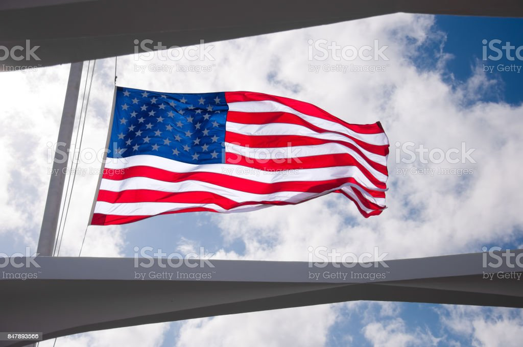 American Flag flying half mast at the USS Arizona Memorial stock photo