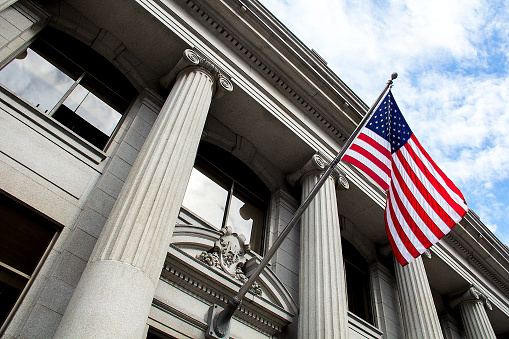 Stone granite official government building in city with American flag waving and flying in the wind, looking up, outside, judicial, freedom, civil courts, columns, criminal justice, law