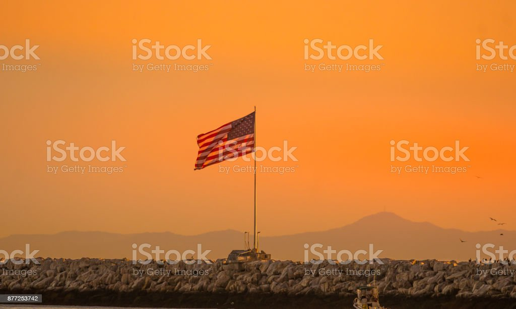 American flag flying over rocky jetty during sunset stock photo