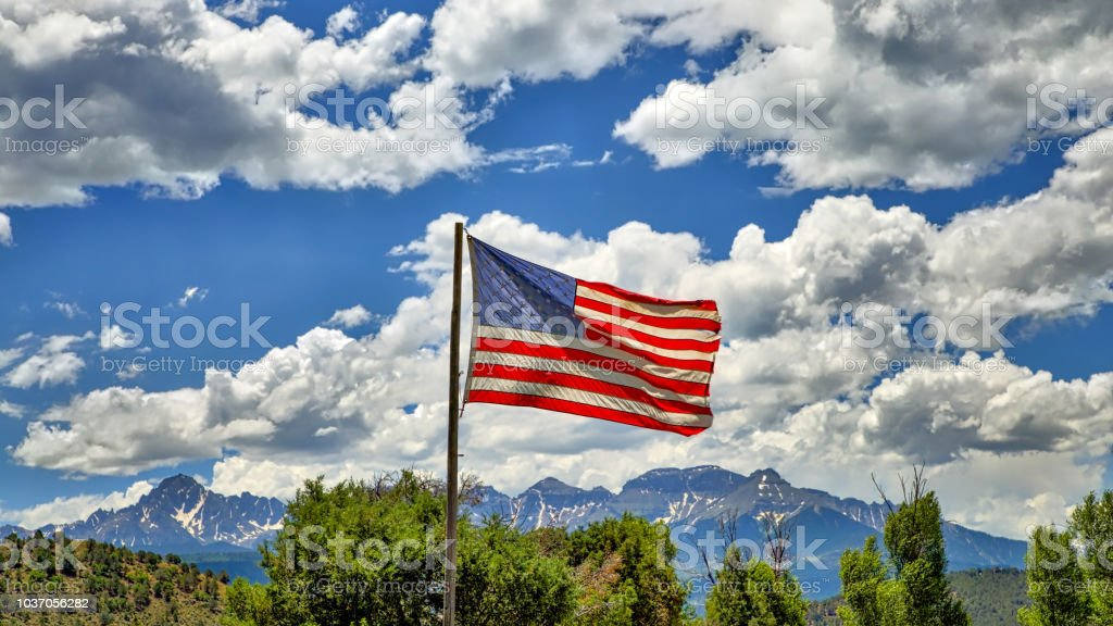 American Flag Flying with Beautiful Sky and San Juan Mountains in Background stock photo