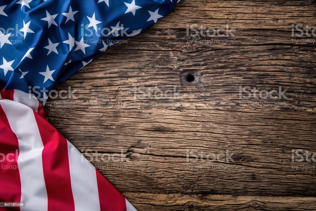 American flag freely lying on wooden board. stock photo