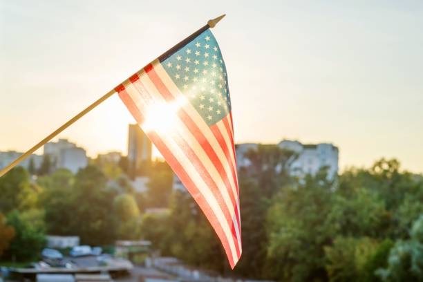 American flag from the window on sunset background stock photo