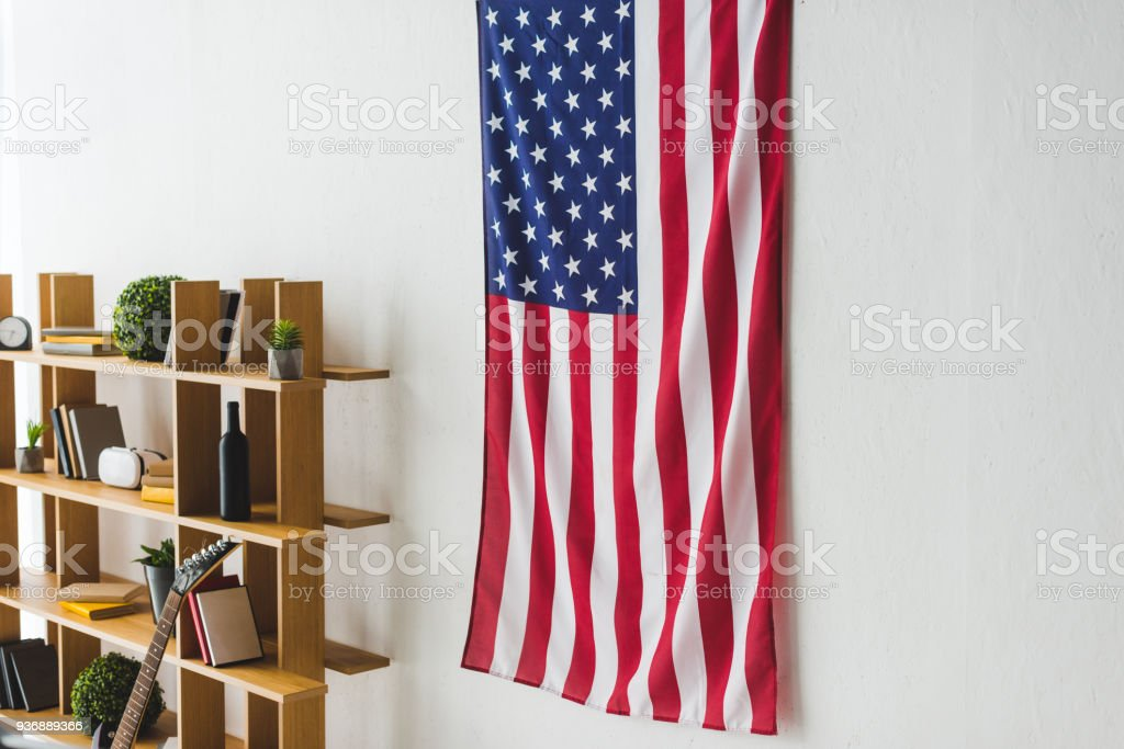 American flag hanging on wall inside living room stock photo