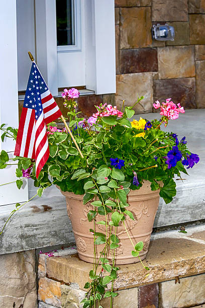 American flag in a plant pot outside a house stock photo