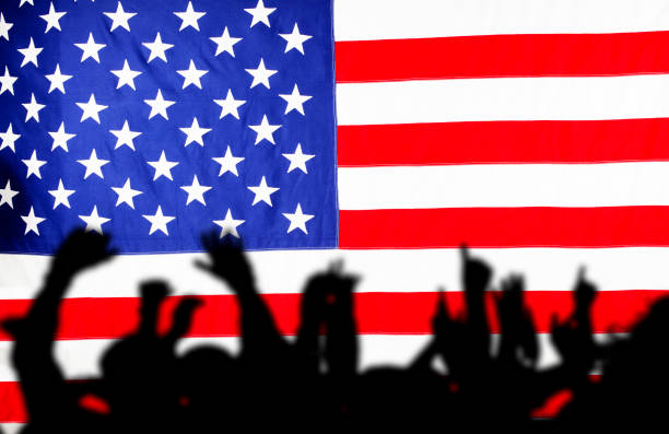 American flag in focus, crowd of people in foreground in soft focus. American flag background.  Crowd in foreground could be praising or rioting. covid stock pictures, royalty-free photos & images