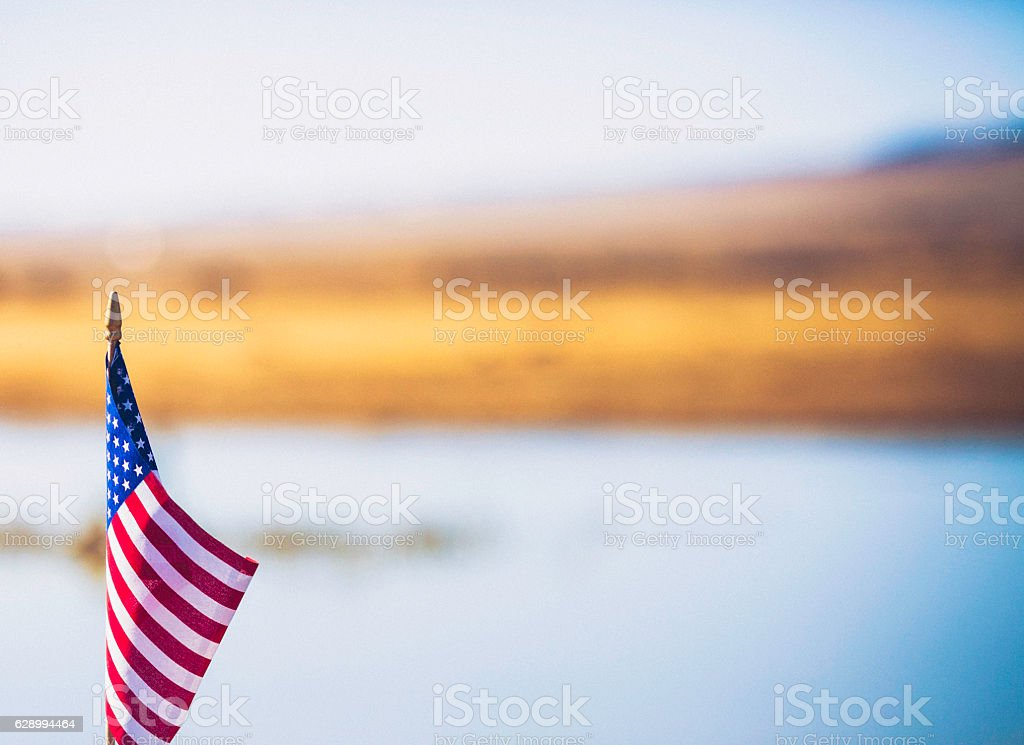 American flag in front of defocused landscape stock photo