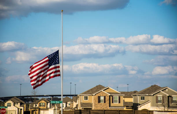 American Flag lowered to Half-Mast with suburb american homes and highway in background stock photo