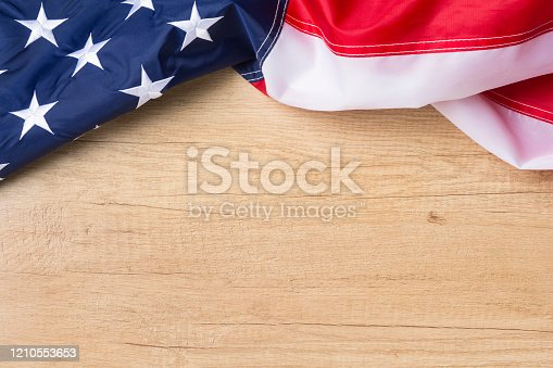 971061452 istock photo American flag lying on a textured wooden background 1210553653