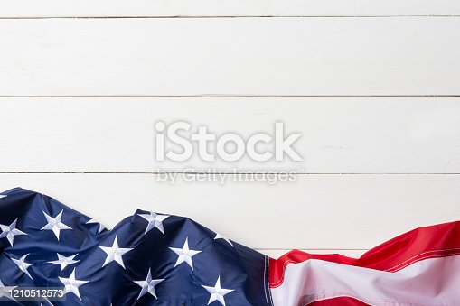 American flag lying on old white wooden background