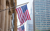 USA symbol in New York streets. American flag on a building, Manhattan downtown, blur Empire state building and scyscrapers on the background