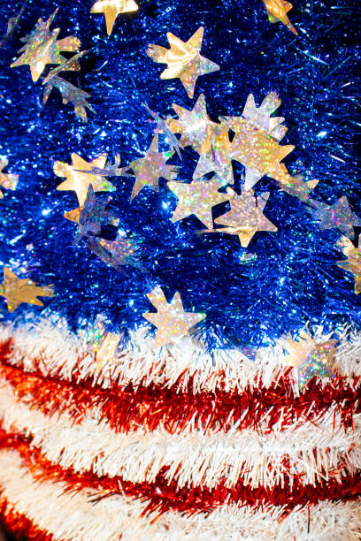 american flag motif in red white and blue tinsel with sparkly stars with a bokeh blur effect - background or design element - fourth of july стоковые фото и изображения