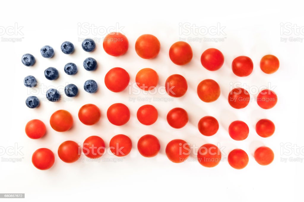 American flag of blueberries and cherry tomatoes on white stock photo
