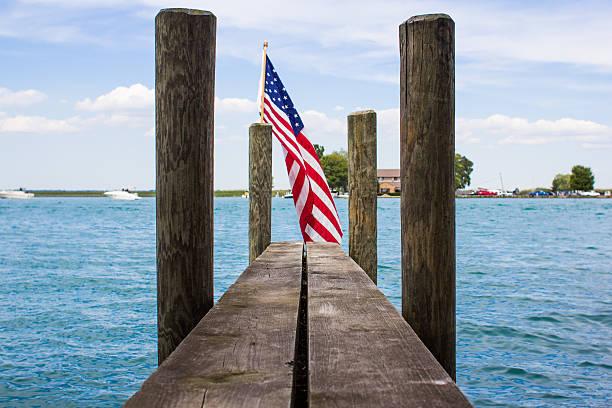 american flag on a hulk with blue sky and lake - 부잔교 뉴스 사진 이미지