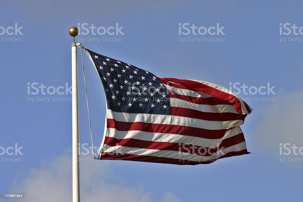 American flag on a pole with a gold orb at the top royalty-free stock photo