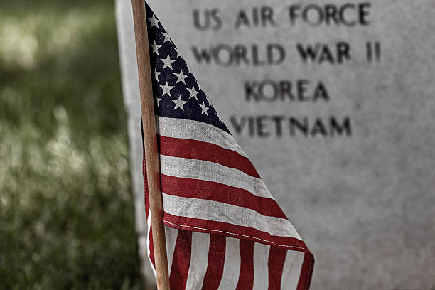 american flag on a soldiers gravesite - arlington national cemetery stock pictures, royalty-free photos & images