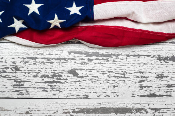 American flag on a white worn wooden background with copy space stock photo