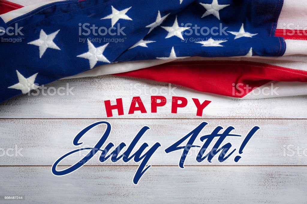 American flag on a white worn wooden background with July 4th Greeting United states flag on white, weathered clapboard background with july 4th greeting Fourth of July Stock Photo