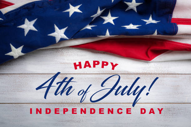 American flag on a white worn wooden background with July 4th Greeting stock photo