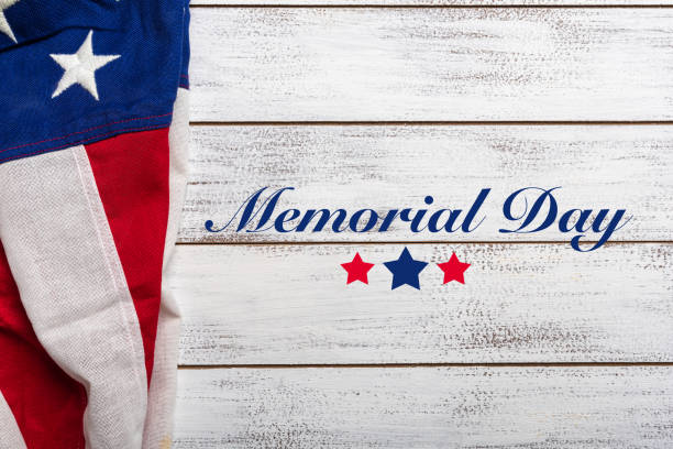 American flag on a white worn wooden background with memorial day greeting stock photo