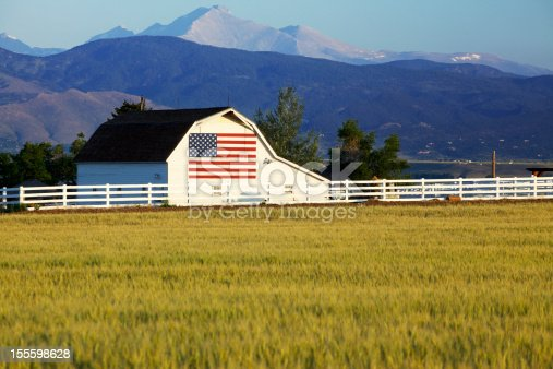 A barn with the American flag painted on the side standing in front of the Rocky Mountains of Colorado. Wheat field in foreground for great copy space.