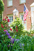 An American flag on a nice brick house with a lush spring garden in front