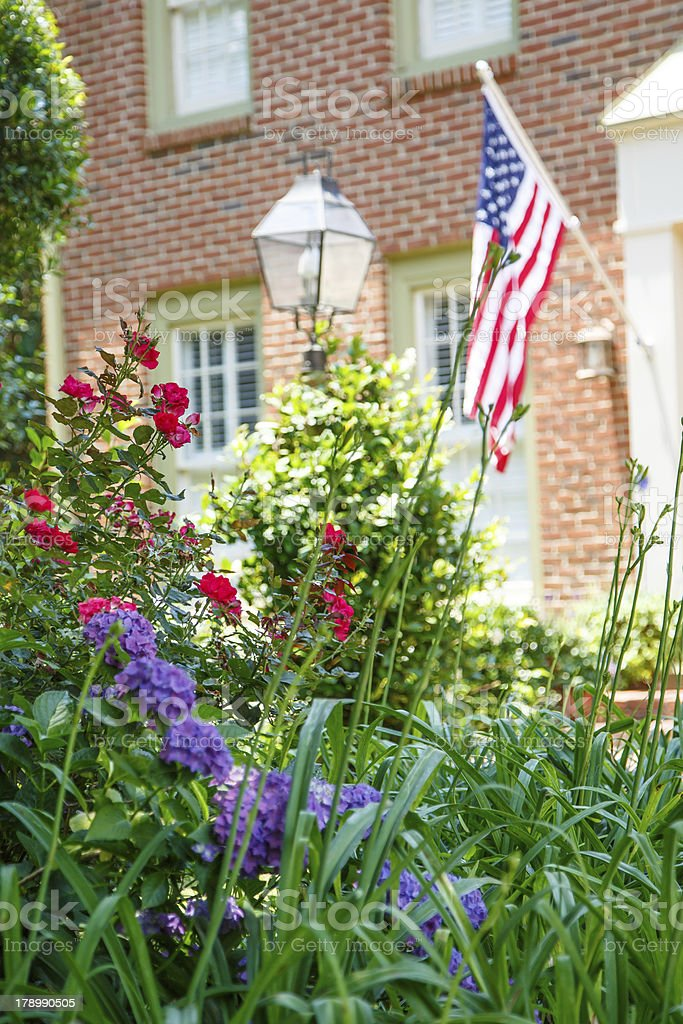 American Flag on Brick Home Behind Garden stock photo
