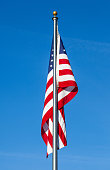 istock American flag on clear blue sky background 500283013