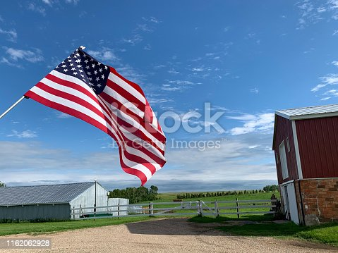 Low angle close up view of American Flag against a blue sky with fluffy white clouds with american farm buildings in background