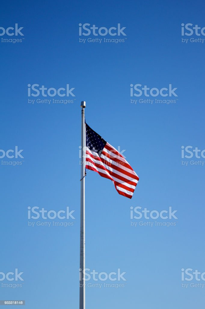 American flag on flagpole with blue sky background stock photo
