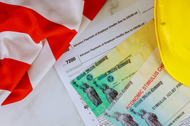 American flag on Stimulus financial relief check to the Passport of USA in hard hat American flag on Stimulus financial relief check to the Passport of USA in yellow hard hat stimulus check stock pictures, royalty-free photos & images